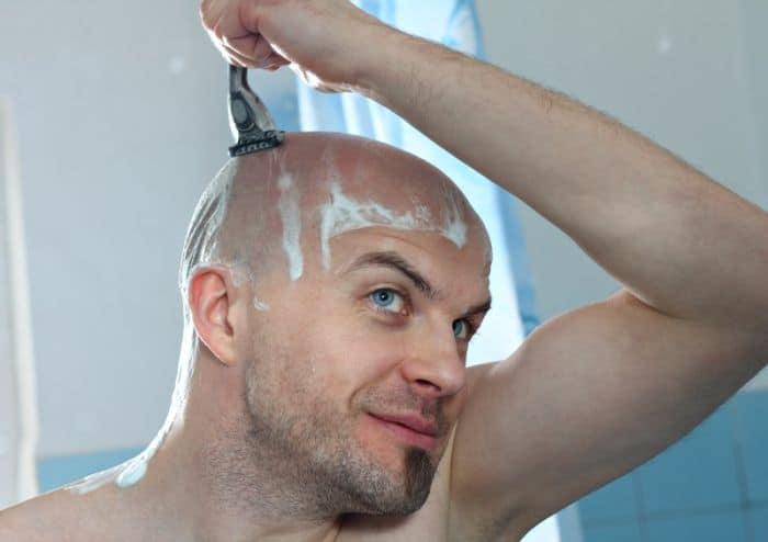 Man shaving head with razor