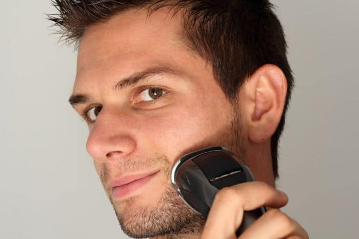 Young man using best electric shaver