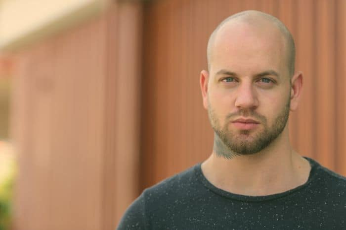 Portrait of young muscular bald bearded man in the streets outdoors