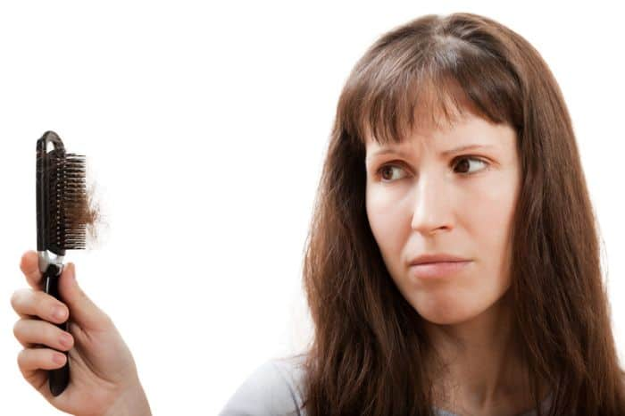 Hair loss in women. Depressed women looking at hair brush with lose hairs