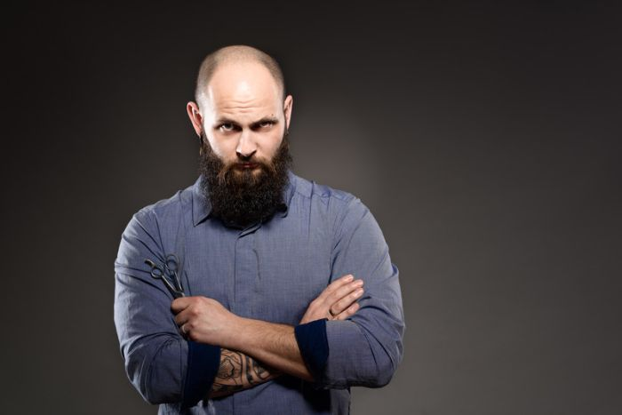 Muscular bearded bald man with tattoo holding scissor