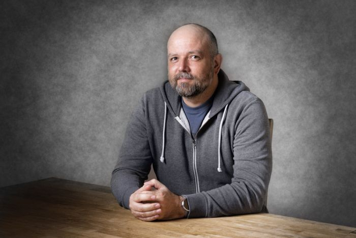 Portrait of a friendly looking, balding bearded man sitting by a wooden table wondering why am I getting bald