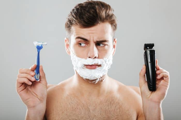 Young man holding an electric shaver vs razor